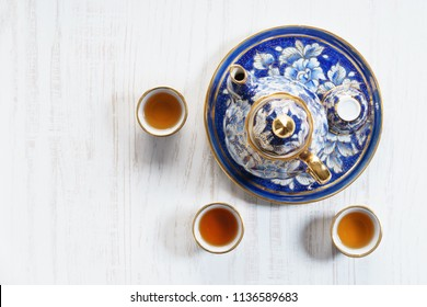Porcelain teapot in classic style on blue color