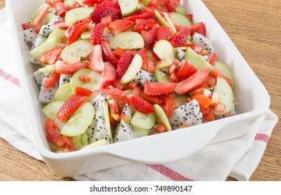 Porcelain Tray of Refreshing Fruits Salad, Strawberries and Dragon Fruits with Cucumbers and Tomatoes.