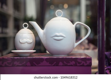 the Porcelain white kettle with a cup in the window of a porcelain shop
