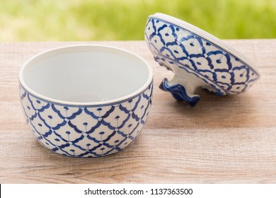 Porcelain white pottery bowl draw a pineapple blue pattern with lid art style asian on  wooden floor In the garden but In parts background tree blur.