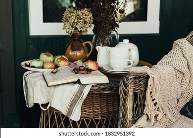 porch of the backyard decorated for teatime with apples and book for reading in autumn