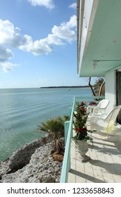 Porch balcony with deep overhang holds white wicker rocking chairs overlooking coral breakwall and walkway on Key Marathon FL.  Atlantic Ocean is calm. Blue sky with light fluffy clouds overhead.