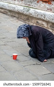 Porch beggar. Beggar old woman with worn clothes sitting outdoors and asking for money help. Social problems.