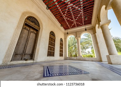 A porch with carved doors and window shutters and tiled flooring at the entrance to a restored traditional arabian house.