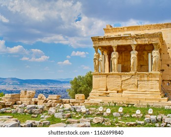 Porch of the Caryatids on the south facade of Erechtheion, ancient temple honoring Athena and Poseidon, at the Athenian Acropolis with the city of Athens in background. Attica region, Greece.