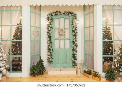 Porch with green door in Christmas decorations and Christmas trees. Spruce garlands around the door. Beautiful winter terrace of the house with garlands of retro light bulbs