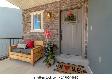 Porch of a home decorated with wooden chair potted plants wreath and doormat