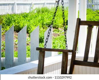 porch swing with garden and white picket fence
