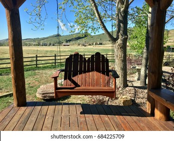 Porch swing in tranquil covered porch rustic country setting