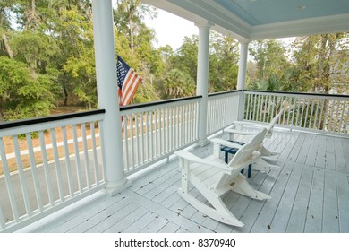 porch with two rocking chairs overlooking street and park