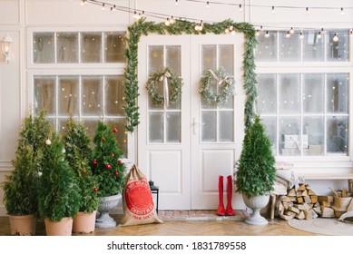 Porch with a white door in Christmas decorations and Christmas trees. Spruce garlands around the door. Beautiful winter terrace of the house with garlands of retro light bulbs - Shutterstock ID 1831789558
