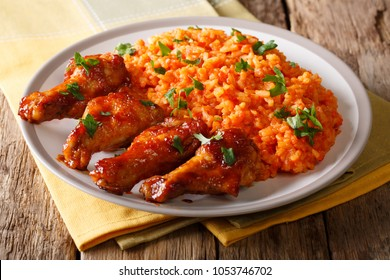 Porcion of African Jollof rice with fried chicken wings close-up on a plate on a table. Vertical top view from above