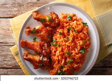 Porcion of African Jollof rice with fried chicken wings close-up on a plate on a table. horizontal top view from above