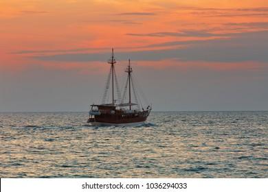POREC, CROATIA - August 16th, 2017: Ship sailing Adriatic sea into sunset
