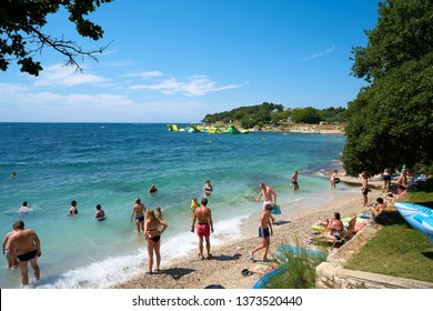 POREC, CROATIA – JULY 17, 2018: Tourists and holidaymakers on the beach of the Adriatic Sea near Porec in Croatia