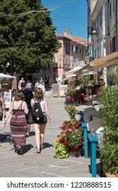 POREC, CROATIA - JULY 20, 2018: Tourists taking a walk through the historic old town of Porec in Istria in Croatia