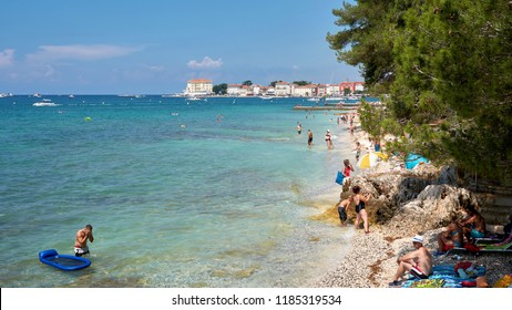 POREC, CROATIA – JULY 22, 2018: bathing tourists on the beach of Porec in Croatia. In the background the old town.