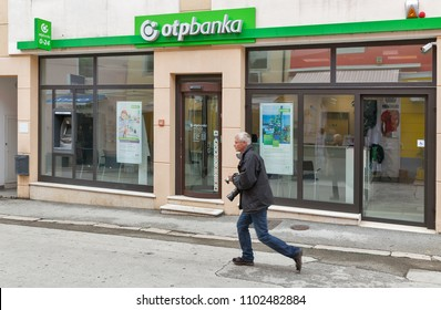 POREC, CROATIA - SEPTEMBER 21, 2017: Man runs along OTP bank facade in Old Town. Porec is a town almost 2,000 years old and municipality on the western coast of the Istrian peninsula.