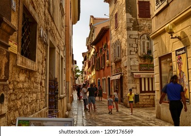 Porec, Istria, Croatia. August 2018. The alleys of the historic center give shade and refreshment during the hottest hours. People enjoy their picturesque charm by strolling.