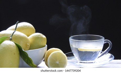 Poring hot water into glass with smoke and lemon sliced on table on black background.hot tea poring concept,healthy drinks