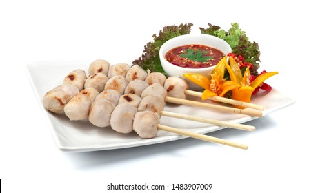 Pork Ball Grilled with bamboo sticks inside dish with seafood spicy sauce dipping decorate with chili peppers Thai food appetizer spicy Thai style side view