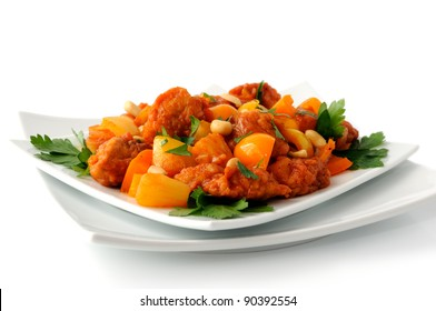 Pork in batter with pineapple and bell pepper in sweet and sour sauce with peanuts