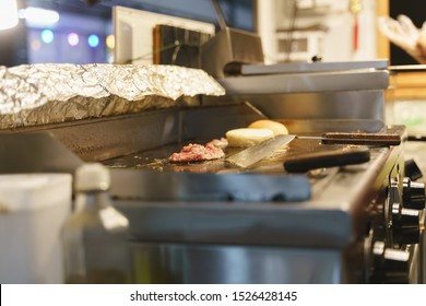 Pork or beef mince meat for burger grilled over modern stove on foodtruck