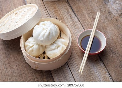 Pork buns in bamboo basket on wooden table