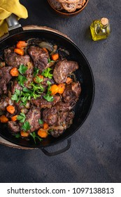 Pork cheeks stewed with vegetables in an iron pan, sliced bread, olive oil, with a dark background in a single shot above. Top view. Vertical copy space. Spanish food.