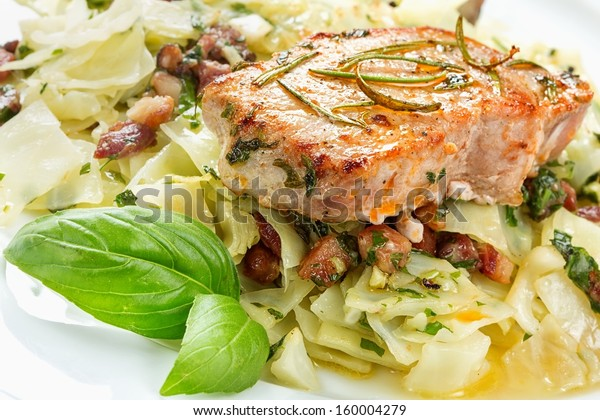 Pork chop with basil pesto, cabbage and bacon