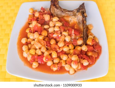 pork chop with a chickpea and tomato, with garlic and onion sauce on a square white plate and yellow place mat