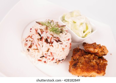 Pork chop (covered in breadcrumbs), three color rice and cucumber salad decorated with dill on a plate on white background