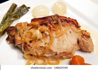 pork chop dish with vegetables, leeks, carrots and onions. pork meat cooked