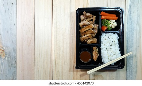 pork chop kurobuta steak Japanese style in bento set on plastic box with wooden background and copy space for label text