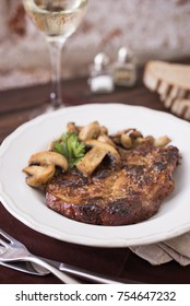 Pork chop with mushrooms and a glass of wine