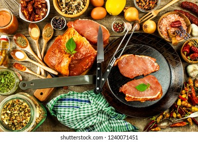 Pork chop on steel pan. Raw meat and spices. Marinated pork meat on grill. Food preparation.