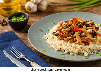Pork chop with peppers, mushrooms and bamboo. Served with rice. Front view.
