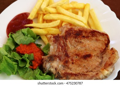 Pork chop served with French fries and chili sauce and ketchup