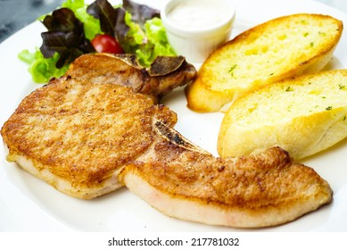 Pork chop served with  garlic bread and salad