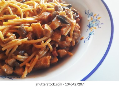 Pork chop with sour cream and mushrooms and spaghetti pasta in a plate