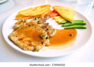 pork chop steak and  gravy  on white dish