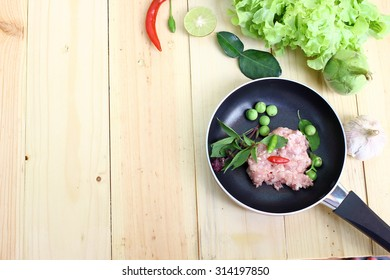 Pork chops and garnish in a pan for preparation of food. Cooking ingredients on a wooden background.
