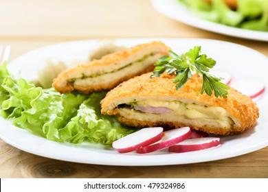 pork cordon bleu with marinated mushrooms and radishes on lettuce leaf