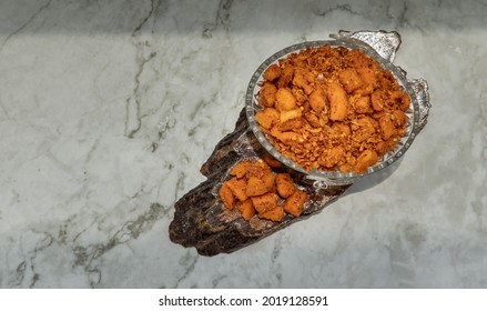 Pork crackling chili paste (Nam prik kag moo) in glass bowl on marble table. Fried chili and Fried Pork Crackling, Thai style food spices and chili dip, Preservation concept, Selective focus.