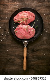 Pork cutlet. Two pieces of raw meat ready for preparation with greens and spices on wooden table.