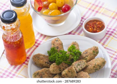 Pork cutlets with hot, sweet, yellow sweet sauces and pickled tomatoes