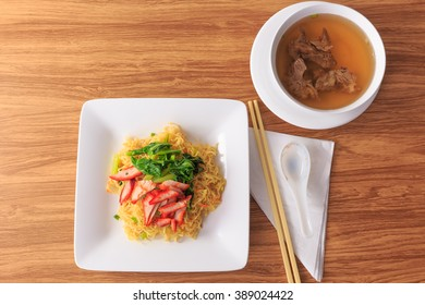 pork dry noodles in white dish on wooden table brown picture closeup soft-focus