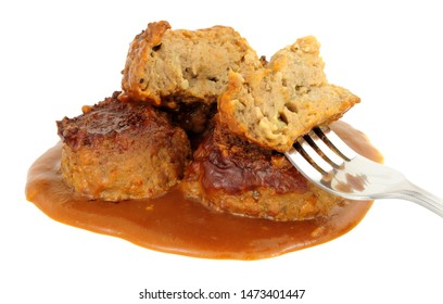 Pork faggots and gravy isolated on a white background