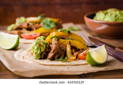 Pork fajitas with onions and colored pepper, served with tortillas and guacamole
