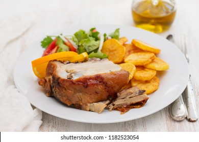 pork with fried potato and salad on white plate